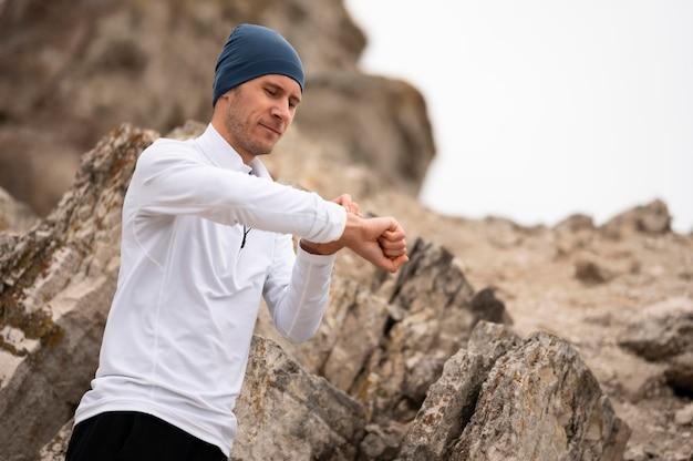 Hombre joven en la naturaleza mirando el reloj cerca de las rocas