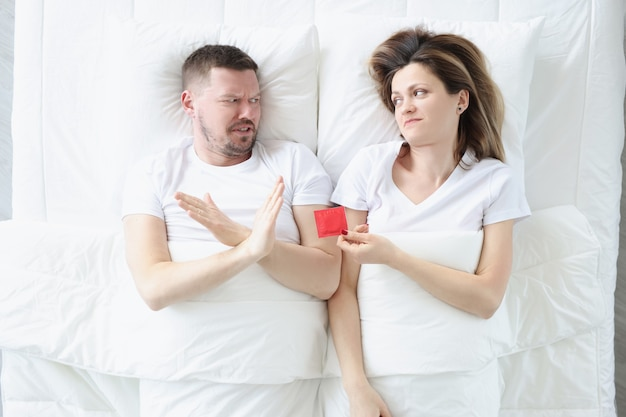 Hombre joven se niega a usar condones mientras está acostado con la mujer en la cama métodos anticonceptivos masculinos