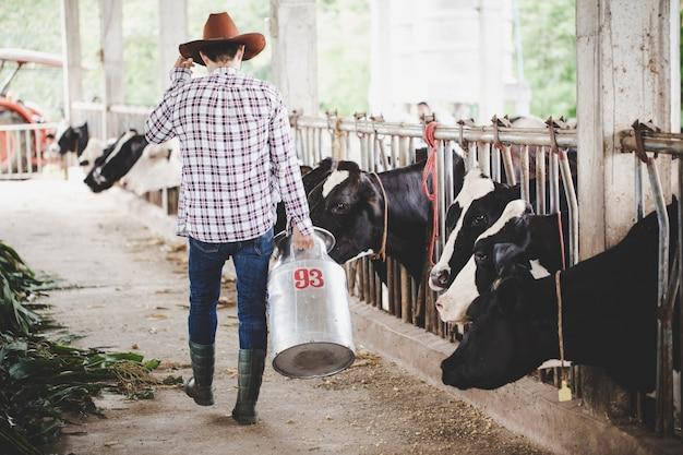 Hombre joven o agricultor con un balde caminando por el establo y las vacas en una granja lechera