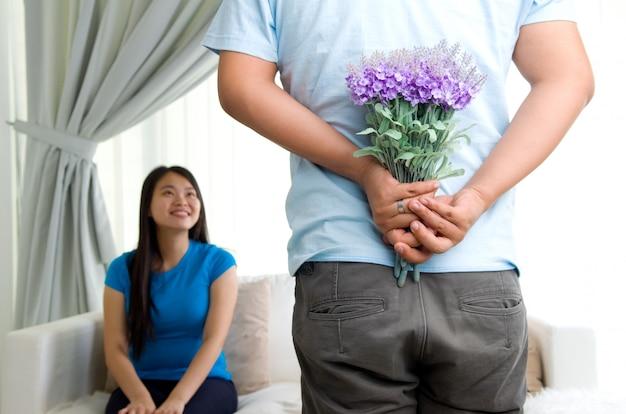 Hombre joven ofreciendo flores a su novia