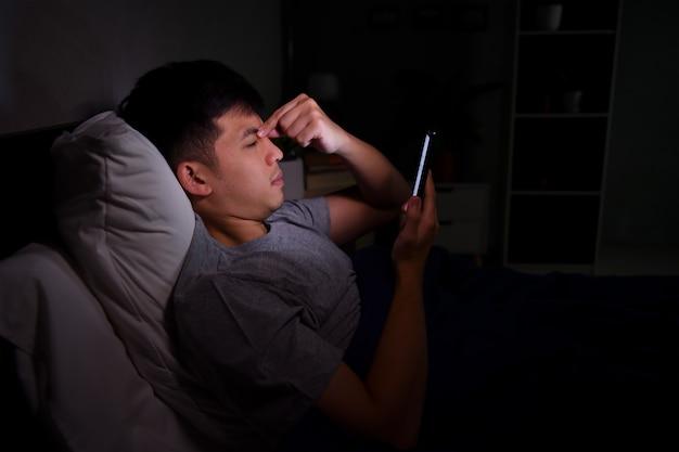 Hombre joven con ojos cansados y doloridos cuando usa el teléfono inteligente mientras está acostado en la cama por la noche