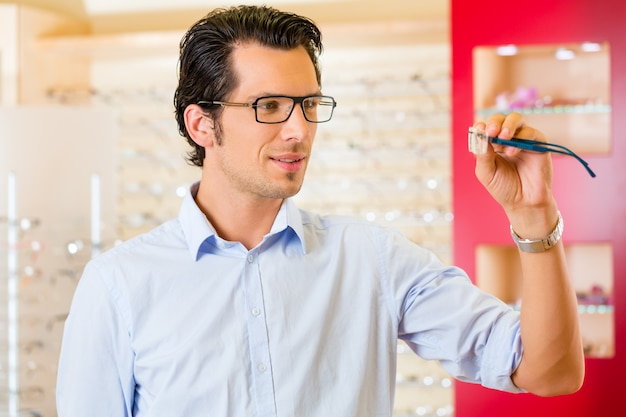 Hombre joven en óptica con gafas