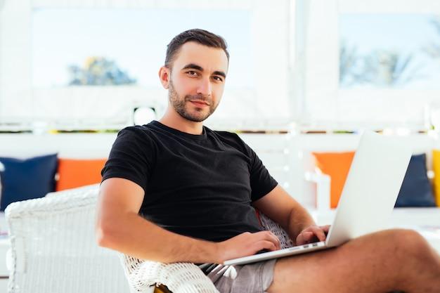 Hombre joven con ordenador portátil en la cafetería al aire libre en las vacaciones de verano