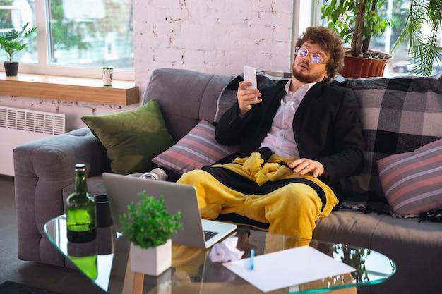 Hombre joven sin pantalones pero con chaqueta trabajando en una computadora, computadora portátil.