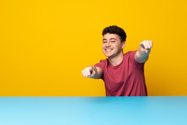 Un hombre joven con una pared y una mesa de colores te señala con el dedo mientras sonríes