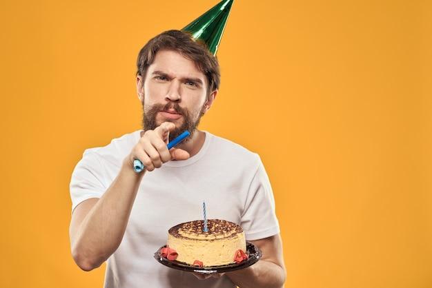 Hombre joven con un pastel de celebración con rebanadas celebra un cumpleaños en una gorra, aislamiento y cuarentena