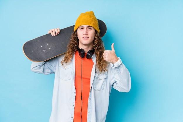 Hombre joven patinador caucásico aislado sonriendo y levantando el pulgar hacia arriba