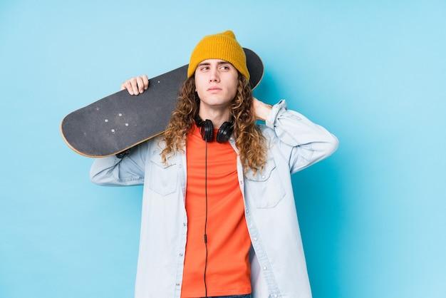 Hombre joven patinador caucásico aislado tocando la parte posterior de la cabeza, pensando y haciendo una elección.