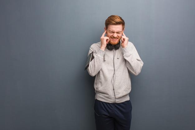 Hombre joven pelirroja fitness cubriendo las orejas con las manos