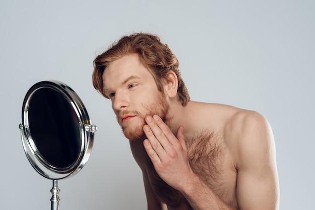 El hombre joven pelirrojo acaricia la barba, mirando en el espejo.