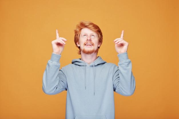 Hombre joven pelirrojo positivo con barba de pie en naranja y apuntando hacia arriba mientras habla de promoción