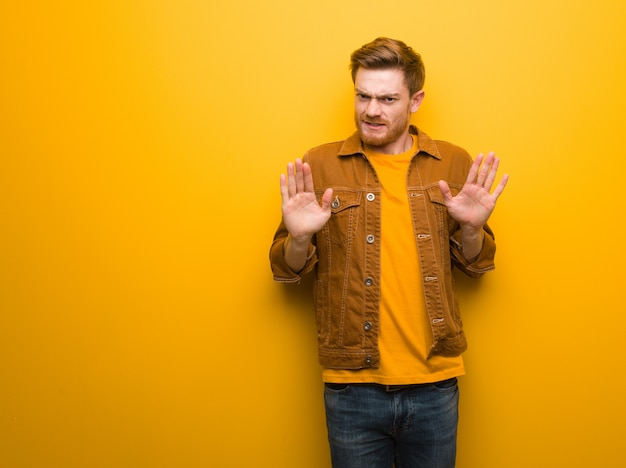 Hombre joven pelirrojo rechazando algo haciendo un gesto de disgusto