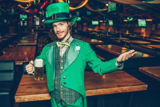 Hombre joven pelirrojo en traje verde con taza de cerveza y mirada. mantiene la mano a un lado.