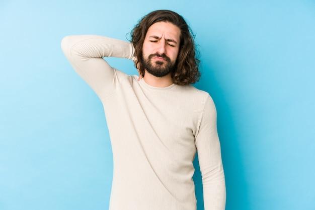 Hombre joven de pelo largo aislado en un fondo azul que sufre dolor de cuello debido al estilo de vida sedentario.