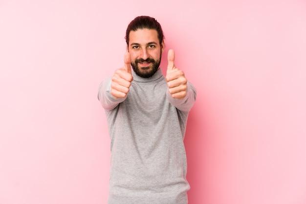 Hombre joven de pelo largo aislado en un fondo rosa con pulgares hacia arriba, aplausos por algo, concepto de apoyo y respeto.