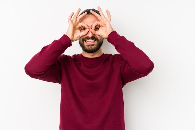 Hombre joven de pelo largo aislado en una pared blanca que muestra signo bien sobre los ojos