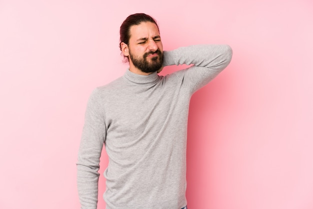 Hombre joven de pelo largo aislado en un rosa que sufre dolor de cuello debido al estilo de vida sedentario.