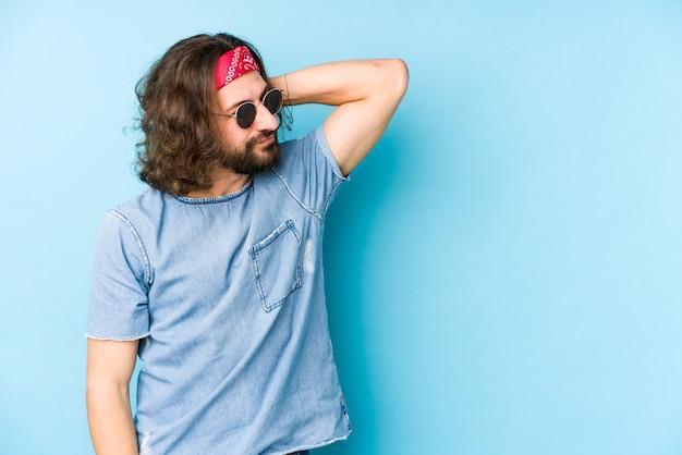 El hombre joven de pelo largo que llevaba un festival hipster mira tocar la parte posterior de la cabeza, pensando y haciendo una elección.