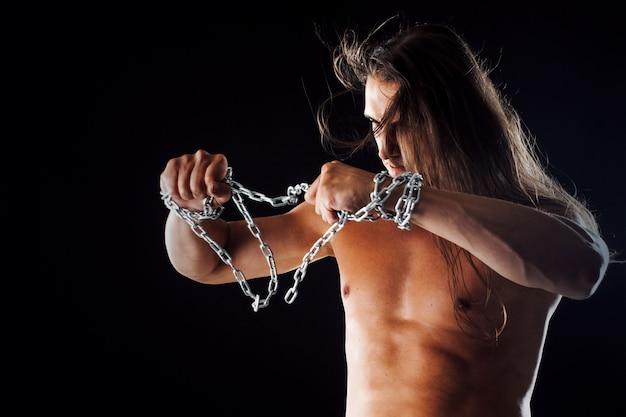 Hombre joven con el pelo largo rompe la cadena de hierro.