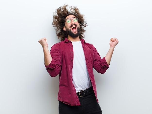 Hombre joven con el pelo loco en movimiento bailando y celebrando