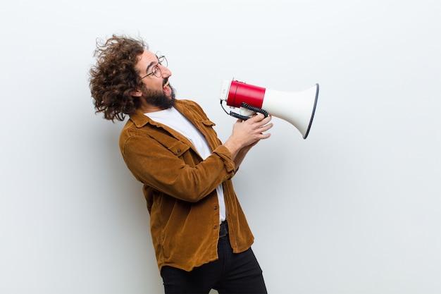 Hombre joven con el pelo loco en movimiento gritando y sosteniendo un megap
