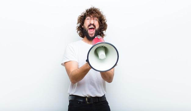 Hombre joven con el pelo loco en movimiento y gritando.