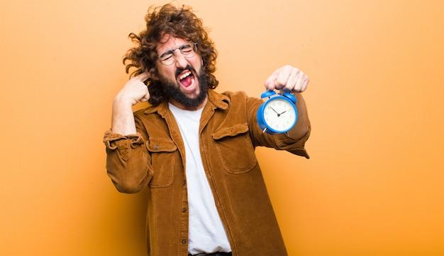 Hombre joven con el pelo loco en movimiento y un reloj despertador
