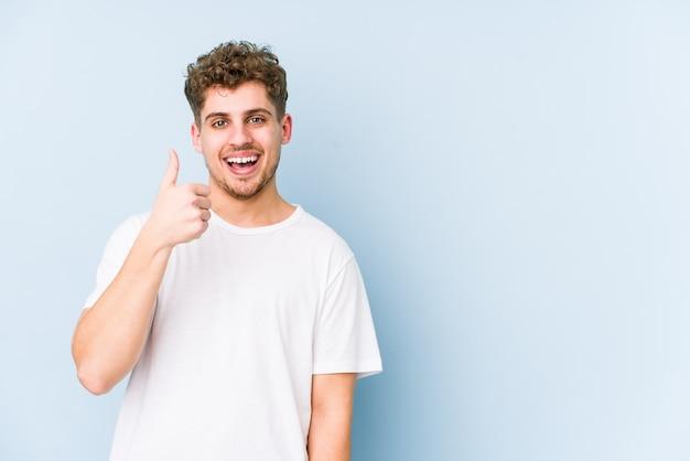 Hombre joven de pelo rizado rubio sonriendo y levantando el pulgar hacia arriba