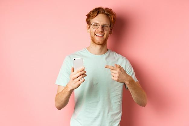 Hombre joven con pelo rojo y barba, con camiseta y gafas, sonriendo mientras señala con el dedo al teléfono inteligente, recomienda promoción en línea, fondo rosa.