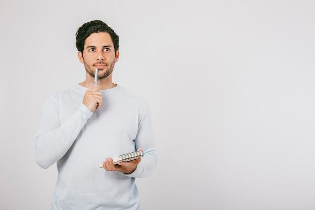 Hombre joven pensando con libreta y bolígrafo