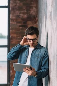 Hombre joven pensativo que se coloca delante de la pared que mira la tableta digital