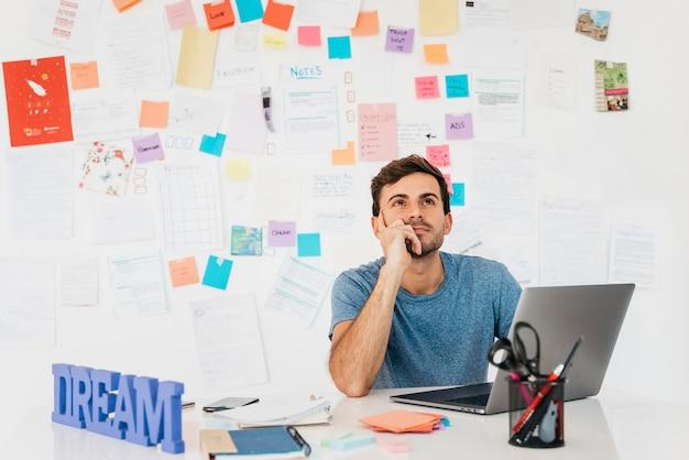 Hombre joven pensativo que se sienta cerca del ordenador portátil contra la pared con las notas