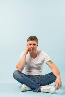 Hombre joven pensativo que se sienta en piso con sus piernas cruzadas contra el fondo blanco