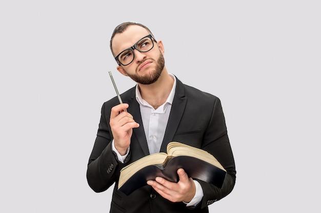 El hombre joven pensativo y serio sostiene el libro y la pluma. él levanta la vista a través de los lentes joven viste traje.