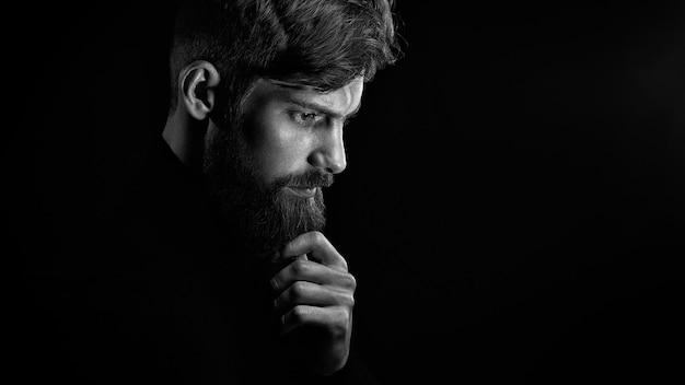 Hombre joven perplejo tocando la barba mirando hacia abajo sobre fondo negro