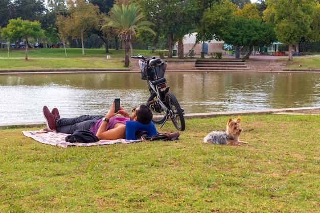Hombre joven con un perro descansa en el parque.