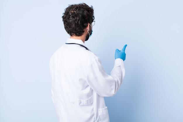 Hombre joven de pie y apuntando al objeto en el espacio de la copia, vista trasera. concepto de coronavirus