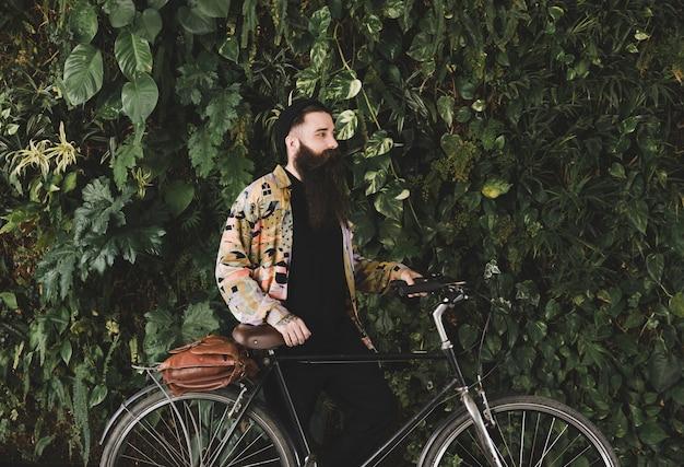 Hombre joven de pie con la bicicleta delante de la pared de las plantas verdes