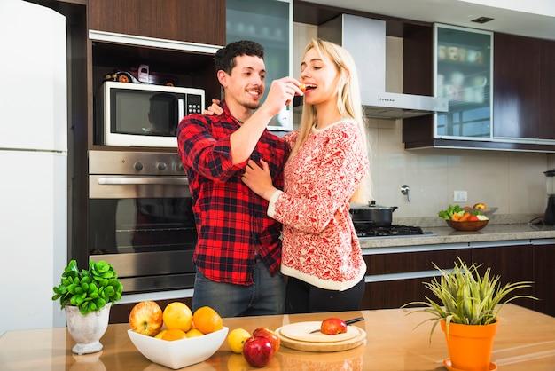 Hombre joven de pie detrás de la mesa de alimentación de fruta rebanada a su esposa
