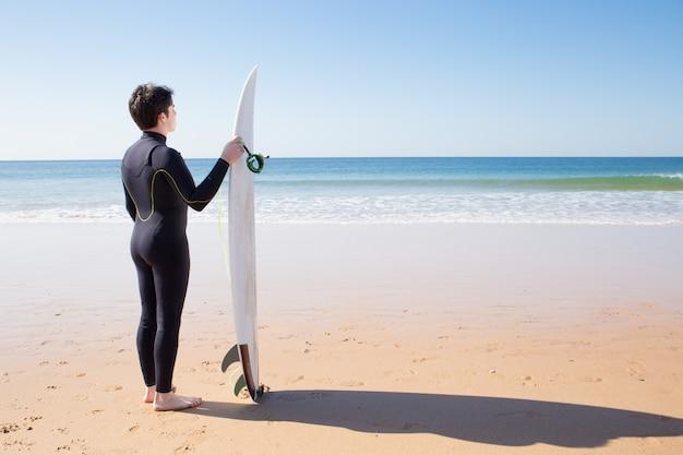 Hombre joven de pie junto a la tabla de surf en la playa de verano