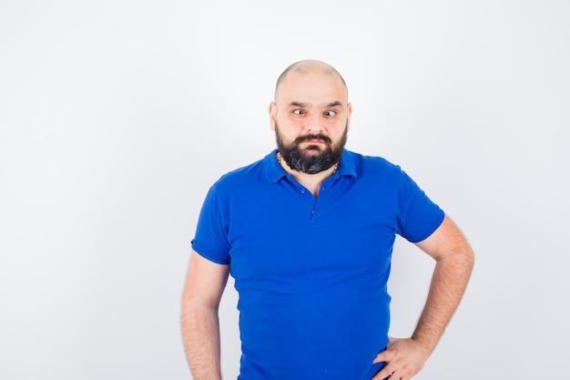 Hombre joven de pie mientras entrecierra los ojos en camisa azul y se ve extraño, vista frontal.
