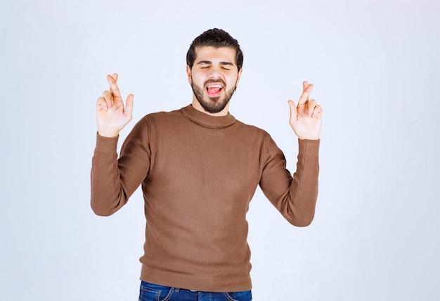 Hombre joven de pie con los ojos cerrados y los dedos cruzados.