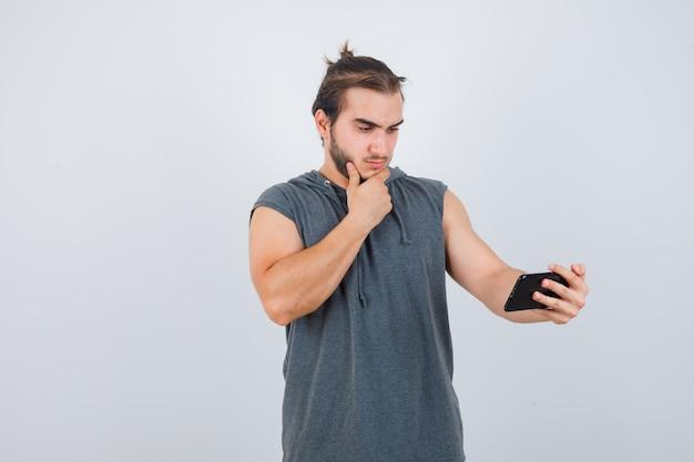 Hombre joven de pie en pose de pensamiento, sosteniendo el teléfono en una camiseta con capucha y mirando sensible, vista frontal.