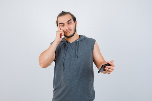 Hombre joven de pie en pose de pensamiento, sosteniendo el teléfono en la mano con una camiseta con capucha y luciendo sensato, vista frontal.