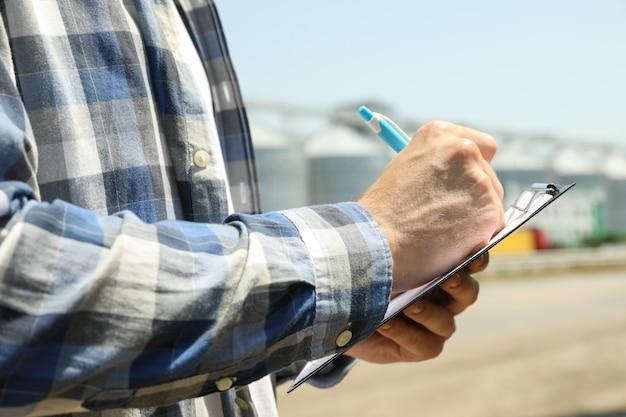 Hombre joven con portapapeles y bolígrafo contra silos de grano. negocio agrícola