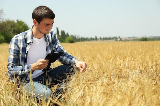 Hombre joven con portapapeles en campo de cebada. negocio de la agricultura