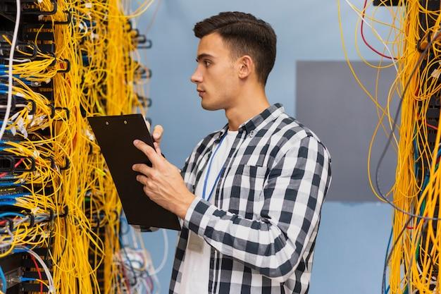 Hombre joven con un portapapeles en la sala de servidores