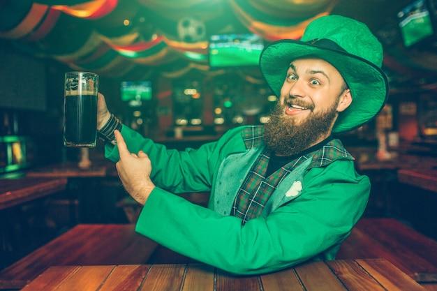 El hombre joven positivo y alegre en traje verde se sienta a la mesa en pub. señala la taza con cerveza oscura. guy se ve feliz.