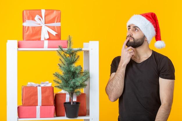 Hombre joven positivo con barba y sombrero de santa claus está de pie junto a la cabina con regalos y árbol de navidad sobre fondo amarillo. concepto de regalo de felicitación y descuentos para navidad y año nuevo.