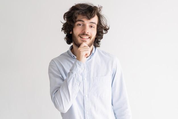 Hombre joven positivo tocando la barbilla y mirando a cámara